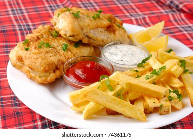 Fish, chips, mayo and ketchup on the white plate
