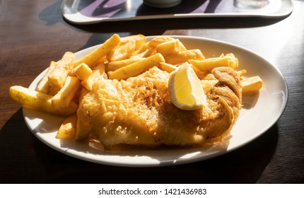 Fish and chips on a plate, battered cod with french fries is traditional british fast food.