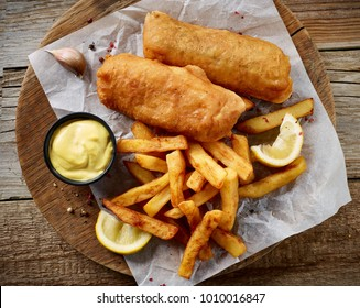 Fish and Chips on wooden table, top view