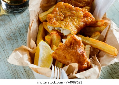 Fish and chips in a paper wrapper. Ruddy crust of batter, lemon slice for squeezing juice. Yummy takeaway food.