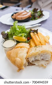 fish and chips served on a white plate with salad and tatar sauce