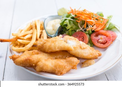 Fish and chips served with salad and sauce
