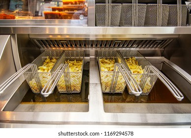 Fish and chips shop deep fat fryer with French fries cut and ready to be lowered into hot cooking oil.