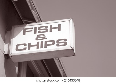 Fish and Chips Sign against Sky Background in Black and White Sepia Tone