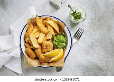 Fish and chips. Traditional british hot dish consisting of fried fish, potato chips, mushy peas and tartare sauce.