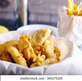 Fish and chips from white fish in paper on wooden background