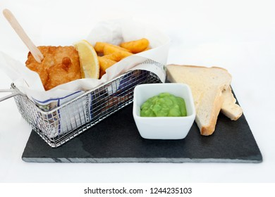 Fish and chips in a wire basket with mushy peas and bread and butter, served on slate plate.