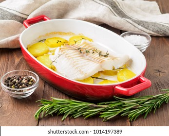 Fish cod baked in the oven with potatoes and spice and thyme - healthy diet healthy food. Dark brown wooden background, side view