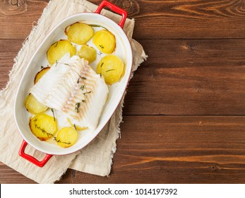 Fish cod baked in the oven with potatoes and spice and thyme - healthy diet healthy food. Dark wooden brown background, top view.