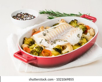 Fish cod baked in the oven with vegetables - healthy diet healthy food. Light white wooden  background, side view.