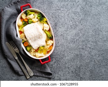 Fish cod baked in the oven with vegetables - healthy diet healthy food. Gray stone background, copy space, top view.