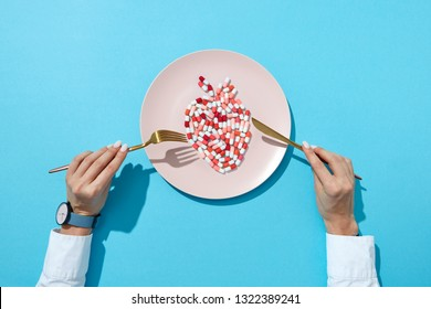 Fish from colorful pills and tablets on a white plate, girl's hands with watch on a blue background with shadows, copy space. The negative effect of pills on cardiovascular diseases. Top view.