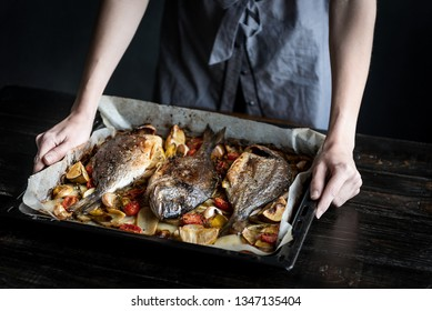 fish for dinner. in female hands baked fish on a baking sheet.