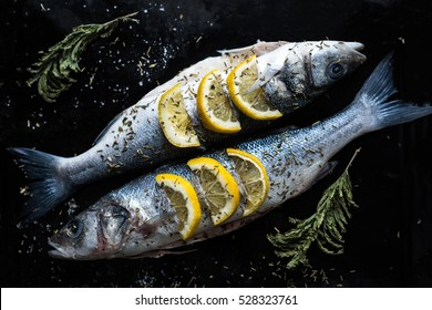 Fish dish cooking with various ingredients. Raw Sea bass with lemon, garlic, herbs and spices on cutting board, top view. Healthy food or diet nutrition concept.