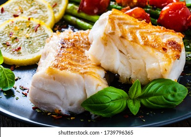 Fish dish - fried cod fillet with asparagus on wooden table