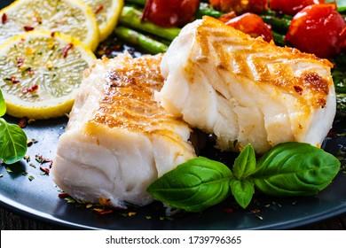 Fischgericht - gebratenes Kabeljaufilet mit Spargel auf Holztisch