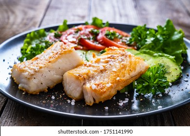 Fish dish - fried cod fillet with vegetables on wooden table