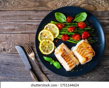 Fischgericht - Frittiertes Kabeljaufilet mit Spargel und Kirschtomaten auf schwarzem Teller auf Holztisch serviert