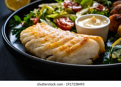 Fish dish - fried cod fillet with potatoes and vegetable salad on black wooden table
