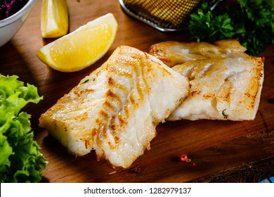 Fish dish - fried fish fillet french fries and vegetables on cutting board on wooden table