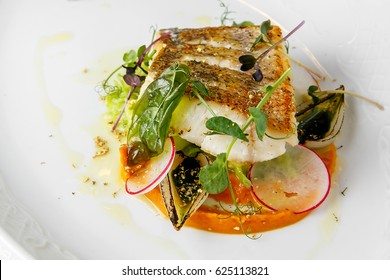Fish dish - fried fish fillet of zander served with tomato, Radish and milk sauce