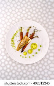 Fish dish in the restaurant - fried fish fillet with vegetables. Art food zender fried fillet with roasted baby carrots, puree and pistachio. Top view