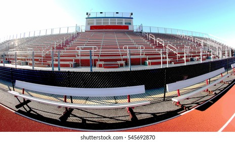 A fish eye photo of a local high school athletic stadium bleechers, benches and track