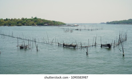 Fish farm with cages for fish and shrimp in the Philippines, Luzon. Fish ponds for bangus, milkfish. Fish cage for tilapia, milkfish farming aquaculture or pisciculture practices.
