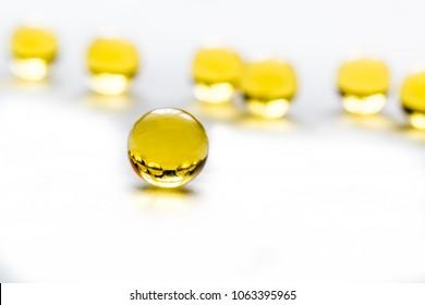 Fish fat round pills on white background, medicine capsule contains omega 3 vitamin