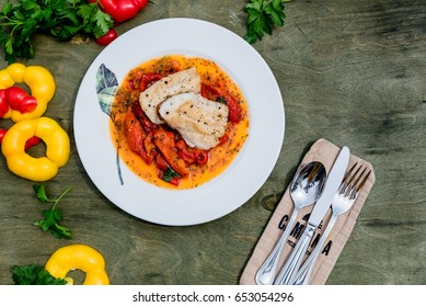 fish fillet with bell peppers in a dish on the table