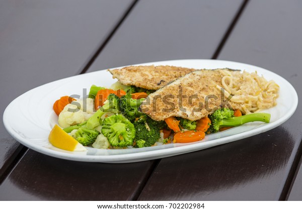 Fish fillet with broccoli, white cabbage and carrot in white plate, close up