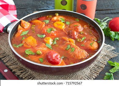 Fish fillet cooked in tomato sauce with green peas and cherry tomatoes on a plate on a wooden background. Healthy eating concept. Easy cooking