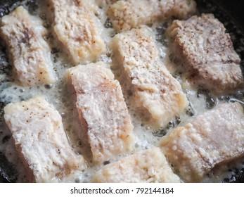 Fish fillet fried in a skillet.