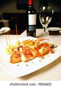 Fish fillet and jumbo shrimp dish with small potatoes