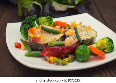 Fish fillet with mixed vegetables. Wooden background. Top view