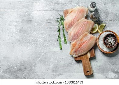 Fish fillet on a wooden cutting Board with rosemary, spices and lemon slices. On white rustic background