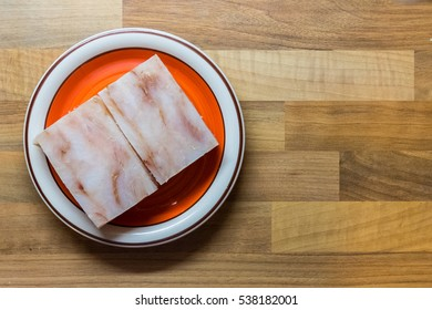 Fish fillets - crushed on plate on the wooden desk - top view