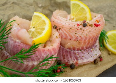 fish fillets of dogfish with lemon herbs on black background