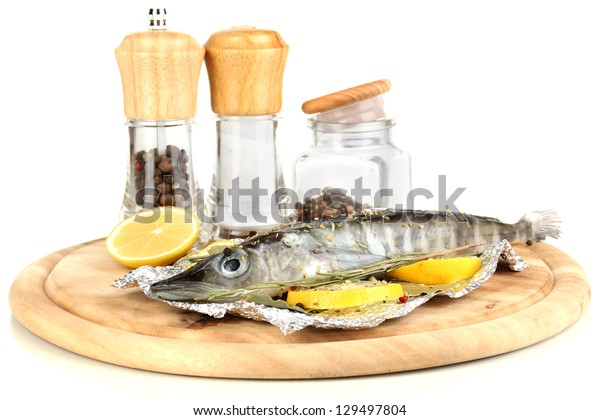 Fish in foil with herbs and lemon on board isolated on white