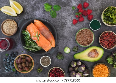 Fish with fresh healthy food ingredients featuring seeds, legumes, fruits and vegetables. Top view, blank space,  rustic surface