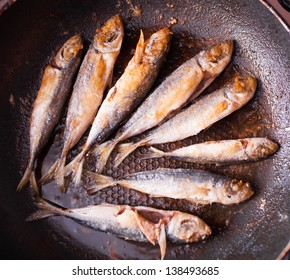 Fish frying on the pan in flour
