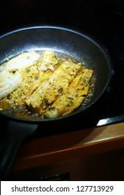 fish frying in a pan