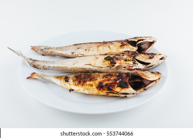 Fish grill dish baked whole grilled on a plate isolated with white background