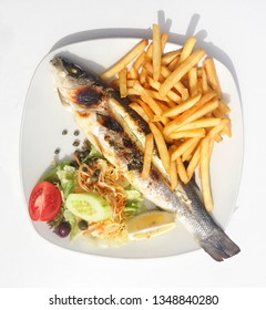 Fish grill with onion, garlic, capper,olives. Baked fish with rosemary, onion, olives, capper and lemon served with chips. Maltese food. Maltese cuisine. Mediterranean cuisine