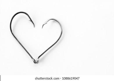 Fish hooks heart shape on white paper background