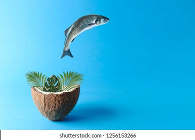 Fish jumping out of palm leaves in coconut. Creative minimal food concept.