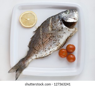 Fish with lemon and tomatoes on white plate