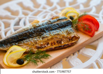 Fish mackerel with golden crust roasted on the grill on a wooden board with lemon and tomatoes and olives