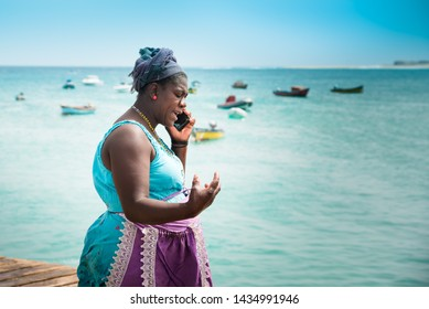 Fish Market, Santa Maria Pier, Sal, Cabo (Cape) Verde Islands - June 16, 2019: Older African woman (fishmonger) in colorful working clothes talks over smartphone on pier. Boats, turquoise sea backdrop