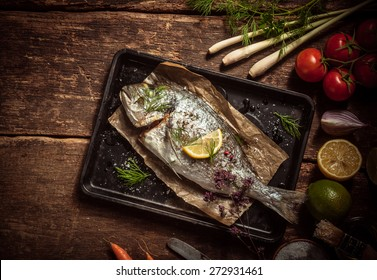Fish Meat on a Black Tray with Herbs and Spices on Top of a Rustic Wooden Table with Organic Veggies. Captured in High Angle View.